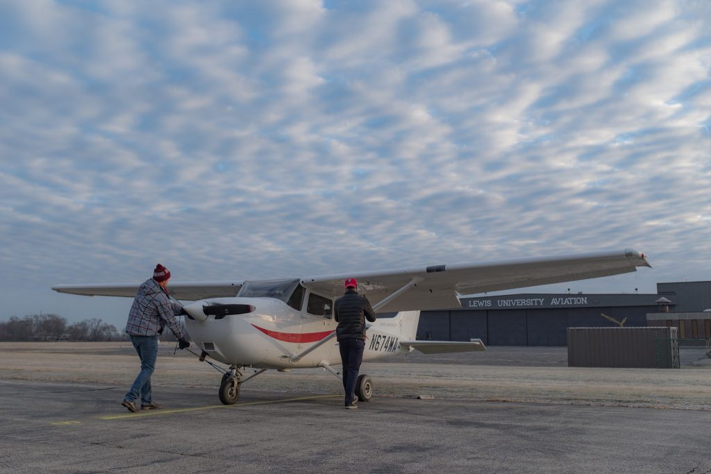 Two men pushing back Cessna 172R tail number N674MA at Lewis University ramp