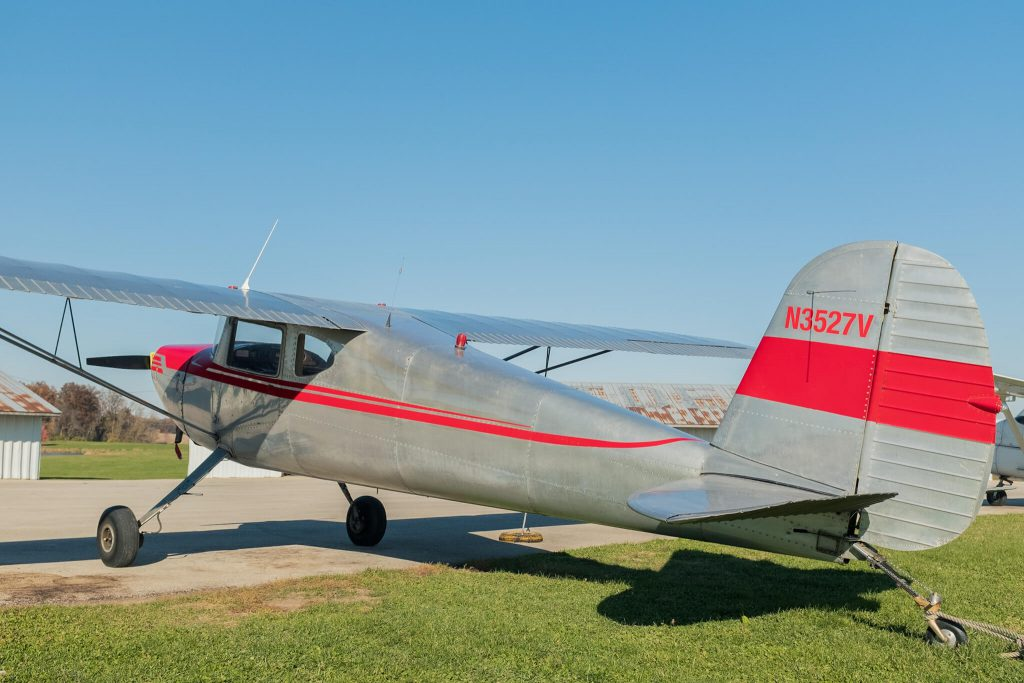 Silver Cessna 140 (N3527V) parked outside hangar at Poplar Grove Airport (C77) on sunny day