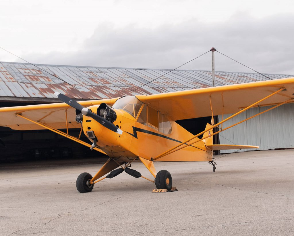 Yellow Piper J-3 Cub (N6673H) parked outside hangar at Poplar Grove Airport (C77) on overcast morning